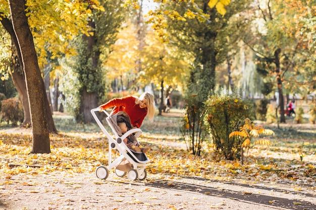 Jeune maman avec une petite fille marchant dans un parc en automne