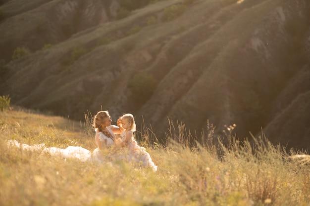 Jeune maman avec une petite fille en robe rose sont assis dans le champ