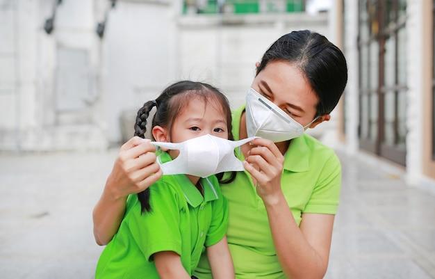 Jeune maman portant un masque de protection pour sa fille à l'extérieur contre la pollution de l'air dans la ville de bangkok