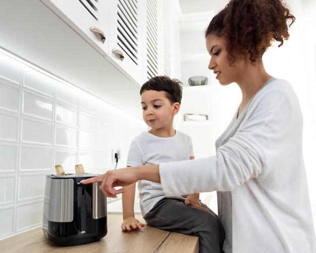 Jeune maman prépare des toasts avec son fils
