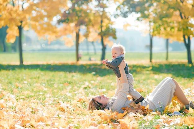 Jeune maman s'amuser avec son charmant enfant dans la nature en journée ensoleillée