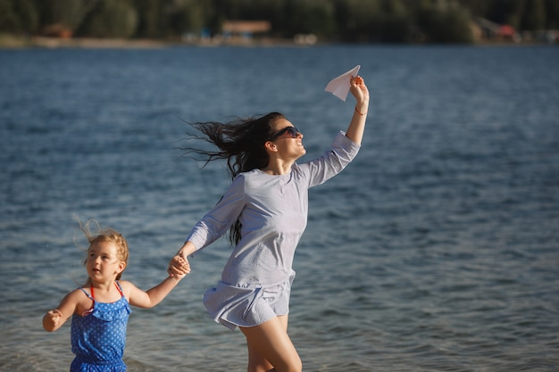 Jeune maman et sa fille mignonne au bord de la mer en lançant des avions en papier dans l'air et en riant