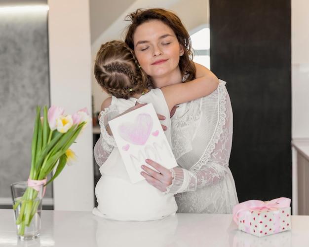 Jeune maman et sa fille s'embrassant tenant une carte de voeux pour la fête des mères