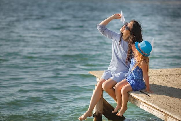 Jeune maman et sa jolie fille au bord de la mer lançant des avions en papier dans l'air et riant. famille joyeuse à la plage