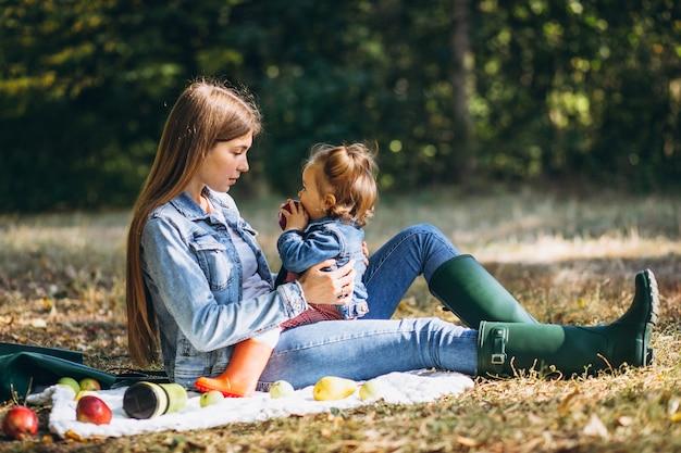 Jeune maman avec sa petite fille dans un parc en automne ayant pique-nique
