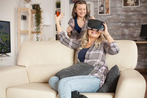 Jeune maman et sa petite fille enthousiasmées par leur nouveau gadget. lunettes de réalité virtuelle.