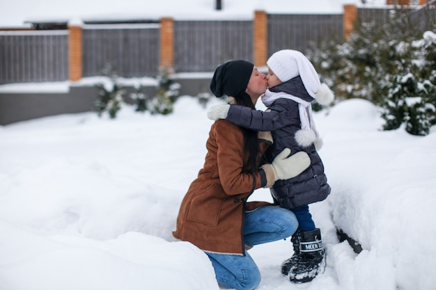 Jeune maman et sa petite fille heureuse s'amuser en plein air sur une journée d'hiver ensoleillée