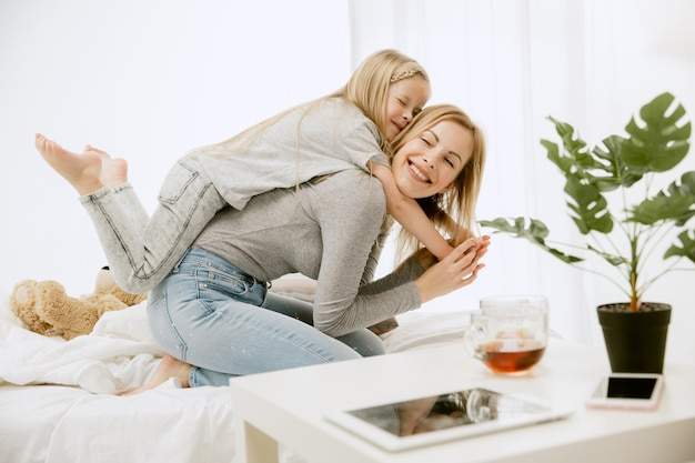 Jeune maman et sa petite fille à la maison au matin ensoleillé. couleurs pastel douces. bon temps en famille le week-end. concept de la fête des mères. concepts de famille, d'amour, de style de vie, de maternité et de moments tendres.