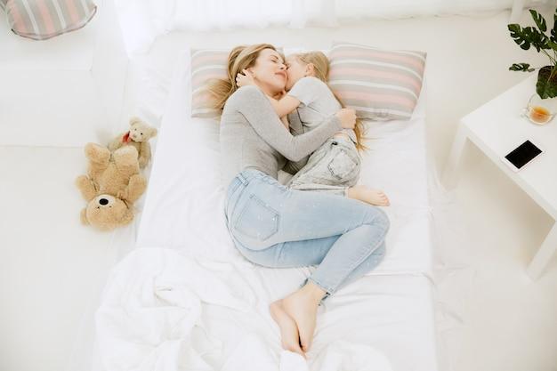 Jeune maman et sa petite fille à la maison au matin ensoleillé. couleurs pastel douces. bon temps en famille le week-end. concept de la fête des mères
