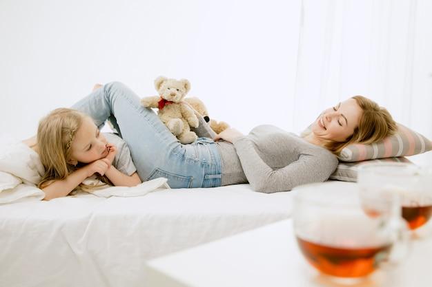 Jeune maman et sa petite fille à la maison au matin ensoleillé. couleurs pastel douces. bon temps en famille le week-end.