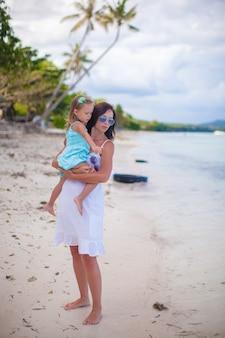 Jeune maman et sa petite fille profitant des vacances à la plage
