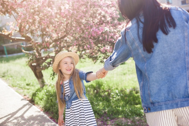 Jeune maman et sa petite fille s'amusant au printemps. belle maman et jolie fille marchant en plein air. famille heureuse ensemble