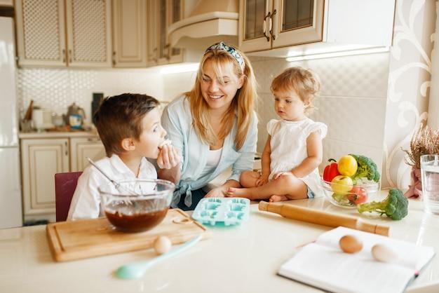 Jeune maman et ses enfants goûte des pâtisseries fraîches avec du chocolat fondu