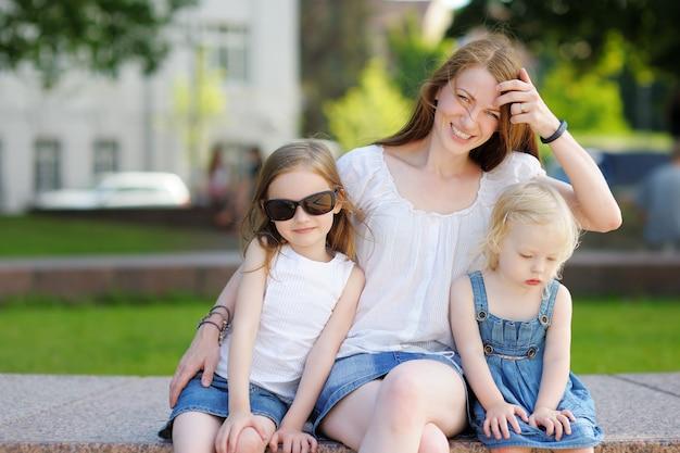 Jeune maman et ses filles en plein air en été