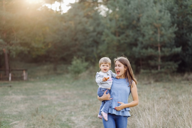 Jeune maman avec son adorable petit bébé en forêt