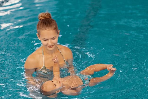 Jeune maman et son bébé bénéficiant d'une leçon de natation bébé dans la piscine. enfant s'amusant dans l'eau avec maman
