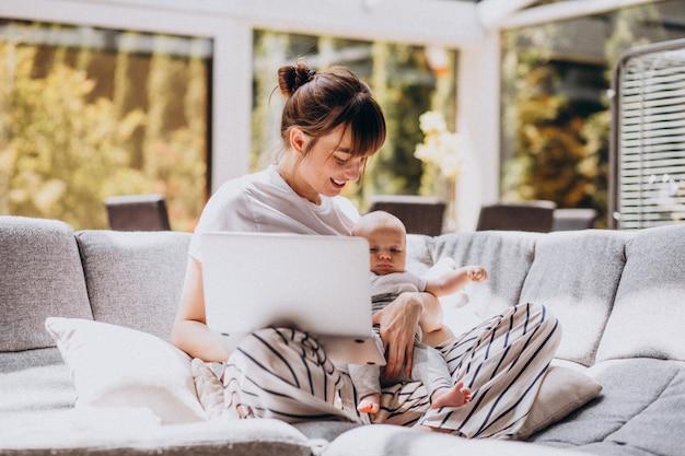 Jeune maman avec son enfant travaillant à la maison sur un ordinateur
