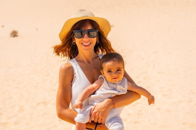Jeune maman avec son fils dans les dunes du parc naturel de corralejo, fuerteventura, îles canaries. espagne