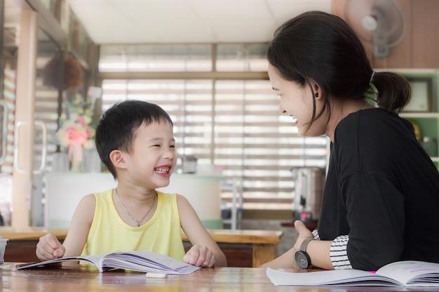 Jeune maman et son fils rigolant rire dans la chambre