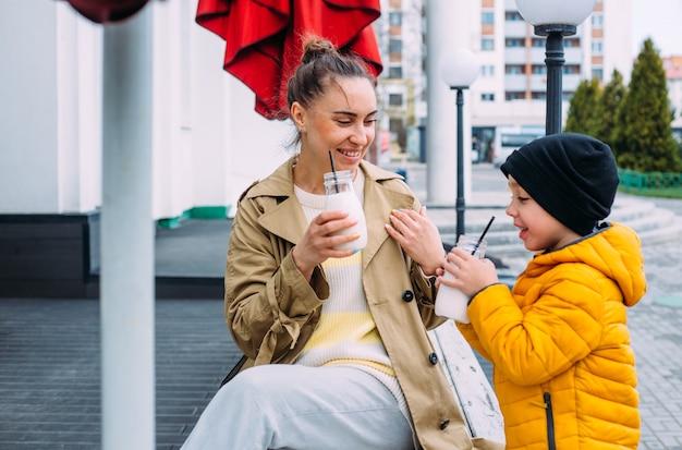 Jeune maman et son fils s'amusent et boivent du milkshake à l'extérieur
