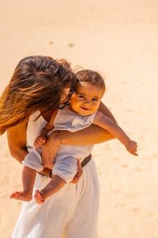 Jeune maman avec son fils très heureux dans les dunes du parc naturel de corralejo, fuerteventura, îles canaries. espagne
