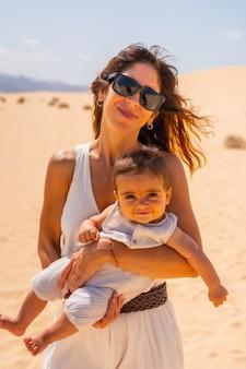 Jeune maman avec son fils en vacances dans les dunes du parc naturel de corralejo, fuerteventura, îles canaries. espagne