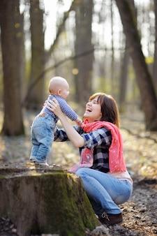 Jeune maman avec son petit bébé dans une forêt de printemps