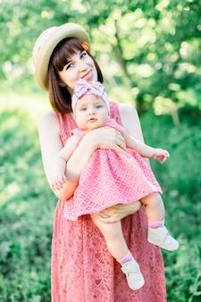 Jeune maman avec son petit bébé sur le pré