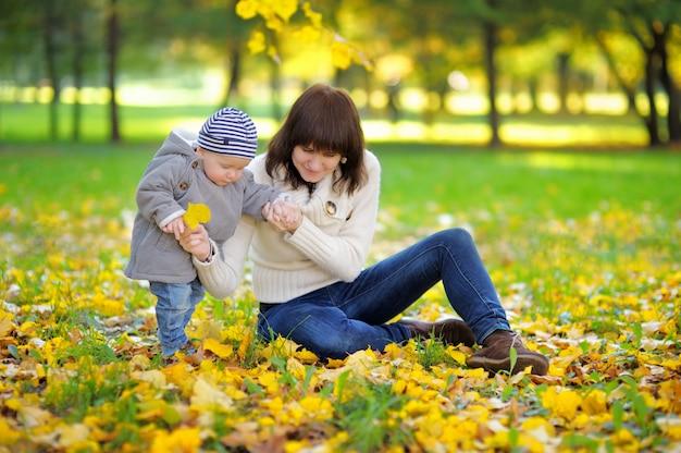 Jeune maman avec son petit bébé s'amuser dans le parc en automne