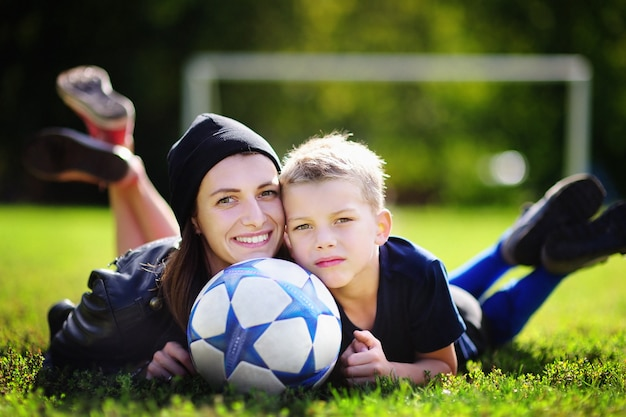 Jeune maman et son petit garçon jouant à un match de football sur une journée d'été ensoleillée. famille s'amuser avec ballon à l'extérieur