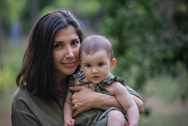 Jeune maman tient bébé dans les bras dans les rayons du coucher du soleil dans le parc.