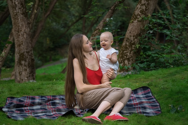 Jeune maman tient bébé sur les mains et assis sur une couverture de pique-nique. pique-nique en famille dans le parc