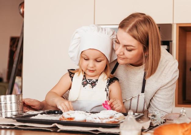 Une jeune maman trompe une petite fille pour cuisiner des petits pains. parent et enfant passent du temps ensemble