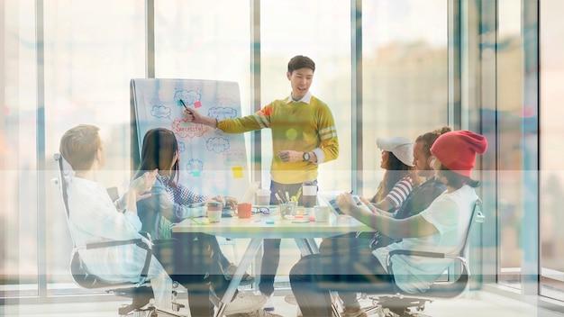 Jeune manager asiatique présentant les idées créatives devant group of asian
