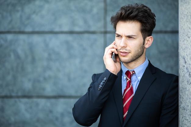 Jeune manager au téléphone en plein air en milieu urbain