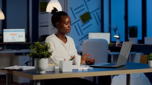 Jeune manager parlant en ligne avec des collègues à distance tard dans la nuit à l'aide d'un ordinateur portable assis dans des heures supplémentaires de bureau d'affaires