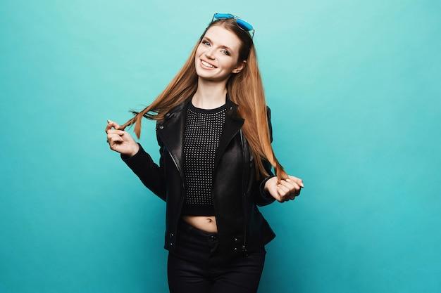 Jeune mannequin blonde femme dans une élégante veste en cuir noir et en jeans noirs posant au bleu clair, isoler. copiez l'espace pour votre texte.