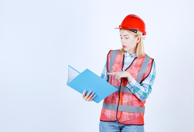 Jeune mannequin blonde montre quelque chose en lisant son fichier à l'intérieur du dossier bleu