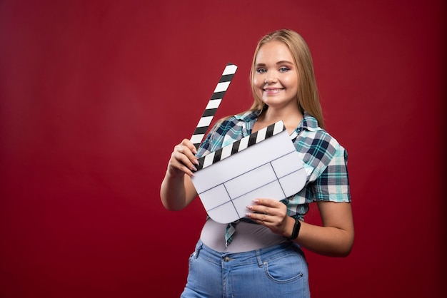 Jeune mannequin blonde tenant un film vierge filmant un panneau de battant et s'amusant.