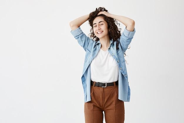 Jeune mannequin brune joyeuse portant un pantalon marron et une chemise en jean, avec une expression rêveuse et joyeuse, jouant avec de longs cheveux ondulés. jeunesse et beauté