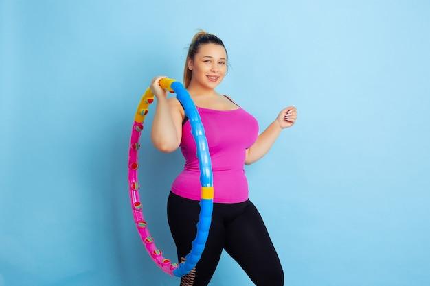 Jeune mannequin caucasien taille plus formation sur fond bleu. concept de sport, émotions humaines, expression, mode de vie sain, corps positif, égalité. faire de l'exercice, poser avec le cerceau.