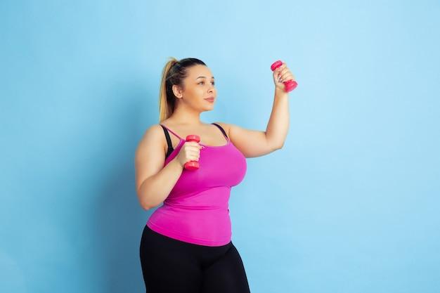 Jeune mannequin caucasien taille plus formation sur fond bleu. concept de sport, émotions humaines, expression, mode de vie sain, corps positif, égalité. formation avec les poids, copyspace.