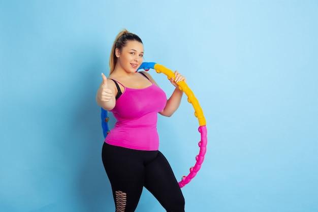 Jeune mannequin caucasien taille plus formation sur fond bleu. concept de sport, émotions humaines, expression, mode de vie sain, corps positif, égalité. posant avec le cerceau, le pouce vers le haut.