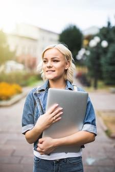 Jeune mannequin debout dans la rue avec un ordinateur portable dans la ville matin d'automne