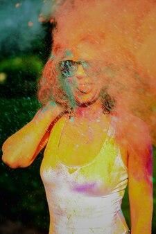 Jeune mannequin drôle s'amusant dans un nuage de poudre sèche orange, célébrant le festival des couleurs holi