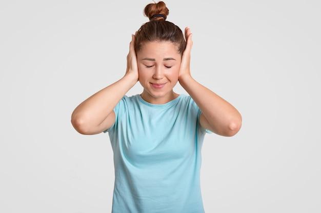 Jeune mannequin femme couvre les oreilles avec les deux paumes, vêtu d'un t-shirt décontracté, évite le bruit fort, a les cheveux noirs peignés en noeud, isolé sur un mur blanc. jolie fille ignore l'écoute de quelque chose