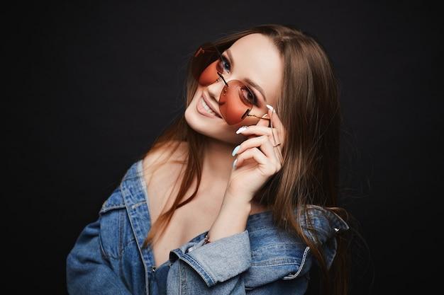 Jeune mannequin femme à lunettes à la mode et veste en jean posant