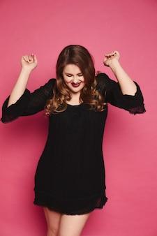 Jeune mannequin grande taille se réjouit et s'amuse à lever les mains sur un mur rose dans le studio isolé