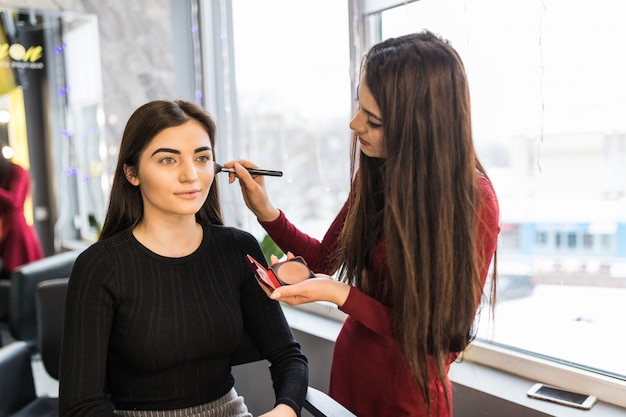 Jeune mannequin avec de grands yeux a une procédure de maquillage