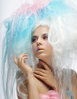 Jeune mannequin avec maquillage lumineux et cheveux colorés